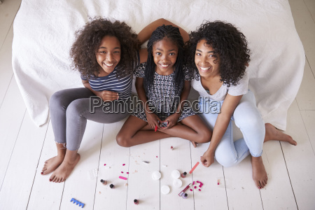 three teenage sisters giving each other
