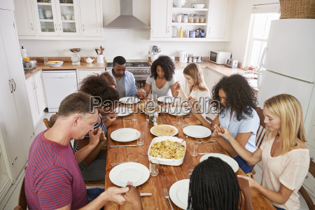 two families saying grace before eating