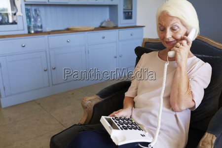 senior woman at home using telephone