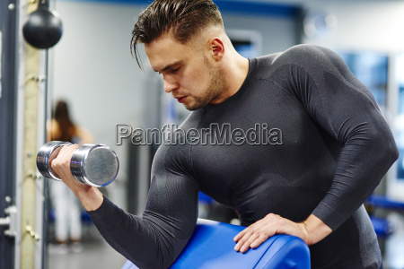 man training with dumbbell in the