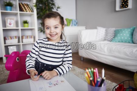 portrait of little girl drawing in