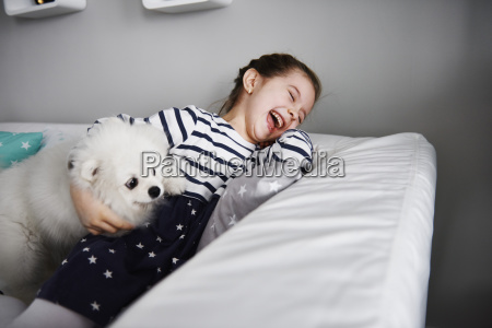 laughing little girl playing with dog