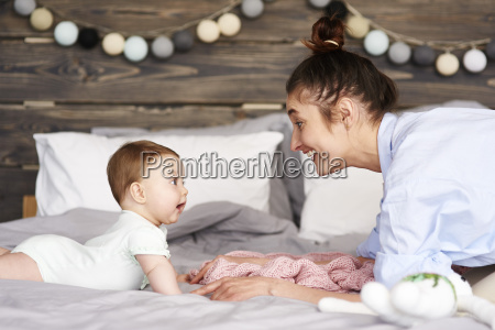 mother and baby playing on bed