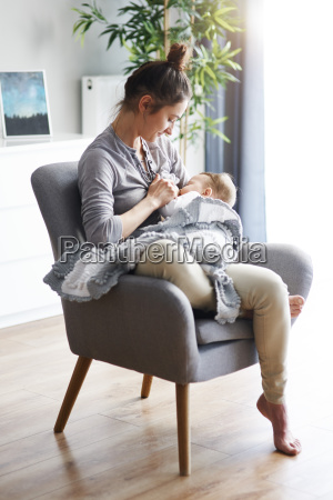 mother sitting on armchair at home