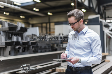 man using tablet on factory shop