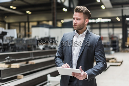 businessman using tablet on factory shop