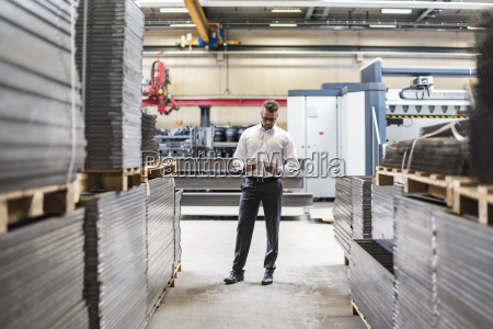 businessman with tablet standing on factory