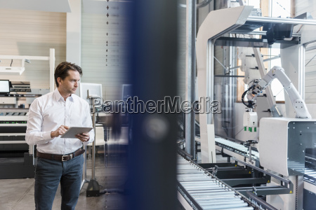 businessman using tablet at conveyor belt