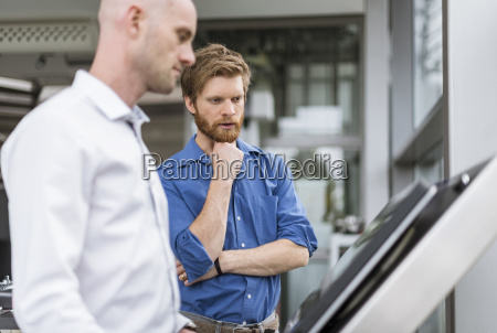 two businessmen in company talking at