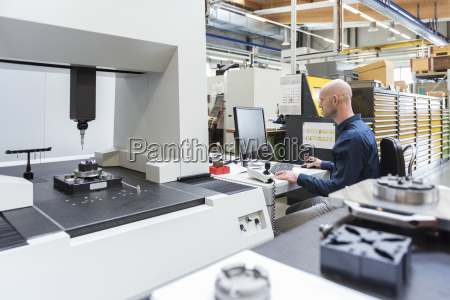 man using computer at machine in