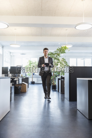 businessman walking in office using digital
