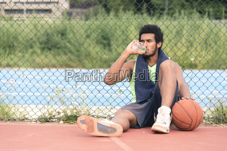 young basketball player drinking from water