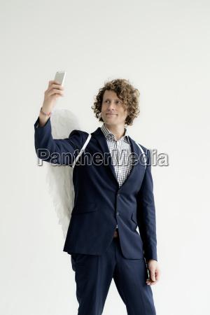 businessman wearing angels wings taking a