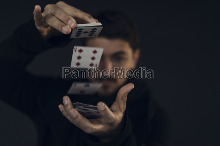 magician conjuring with playing cards close