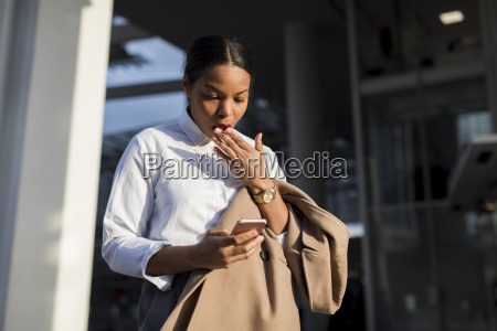 portrait of shocked businesswoman reading email