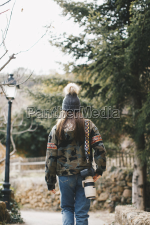 back view of young photographer outdoors