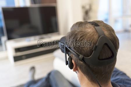 man wearing vr glasses watching tv