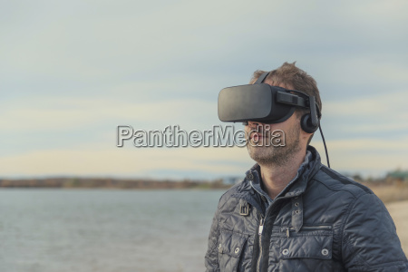 man wearing vr glasses at lakeshore