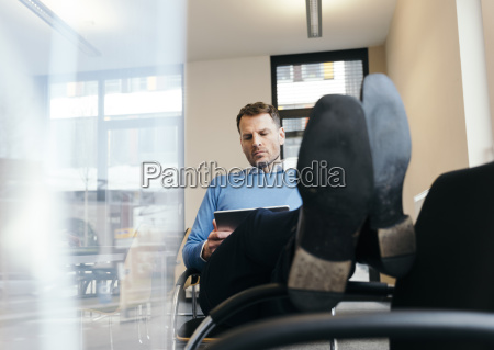 casual businessman using tablet in office