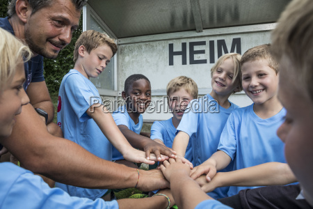 coach and young football players huddling