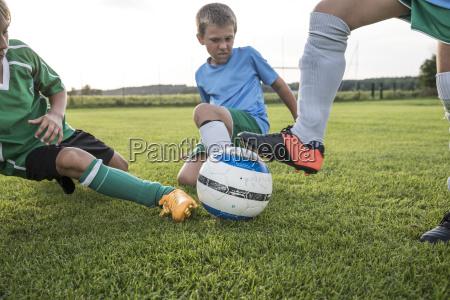 young football players tackling on football