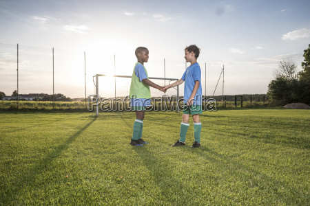 young football players shaking hands on
