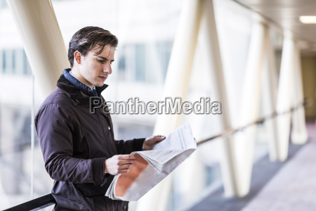 businessman standing in skywalk reading newspaper