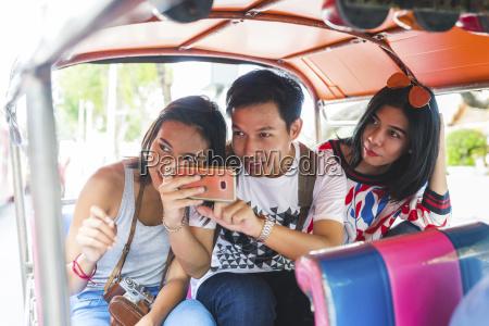 thailand bangkok three friends riding tuk
