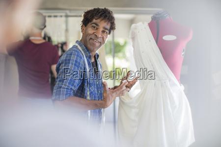 smiling fashion designer presenting dress