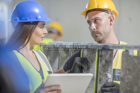 woman with tablet talking to man