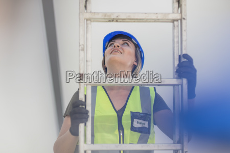 young woman on construction site climbing