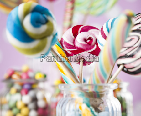 colorful, candies, in, jars, on, table - 25135016
