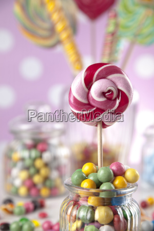 colorful, candies, in, jars, on, table - 25135384