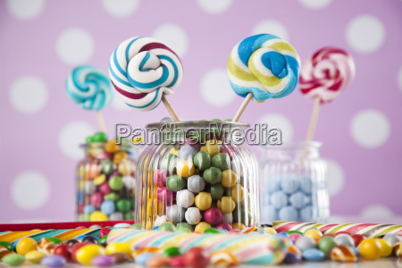 colorful, candies, in, jars, on, table - 25135676