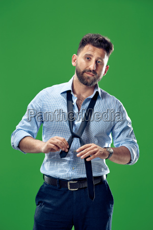businessman tying his tie at green