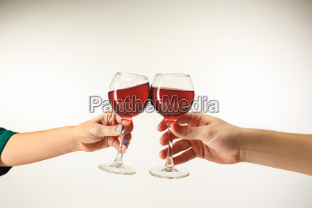 hands with glasses of red wine