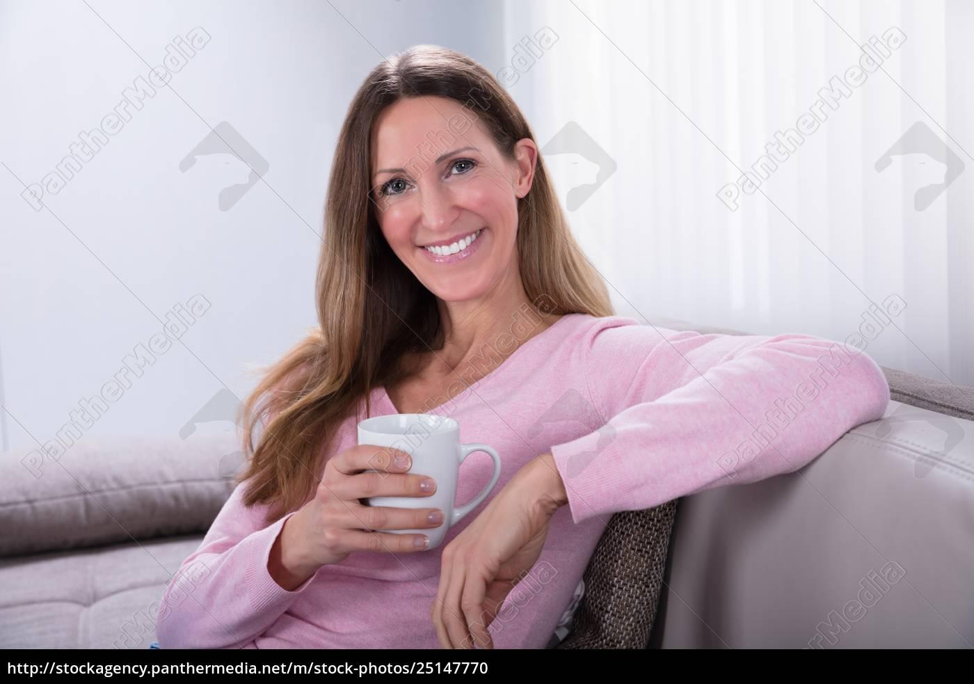 happy, woman, sitting, on, sofa, holding - 25147770