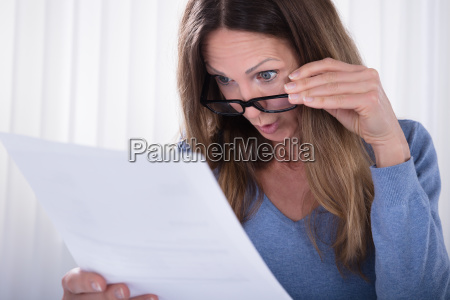 shocked, woman, looking, at, document, in - 25147760