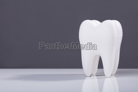 single white tooth on grey background