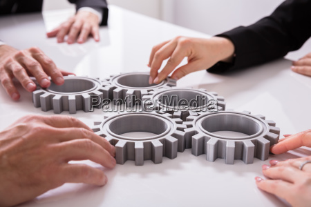 businesspeople joining gears on desk
