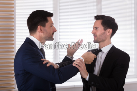 angry, businessman, holding, his, partner's, tie - 25155470