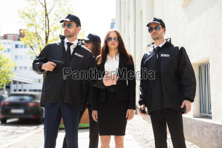 portrait, of, young, businesswoman, with, bodyguards - 25155296