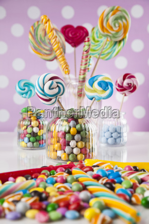 colorful, candies, in, jars, on, table - 25161766