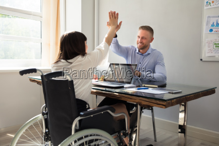 disabled, businesswoman, giving, high, five, to - 25333298
