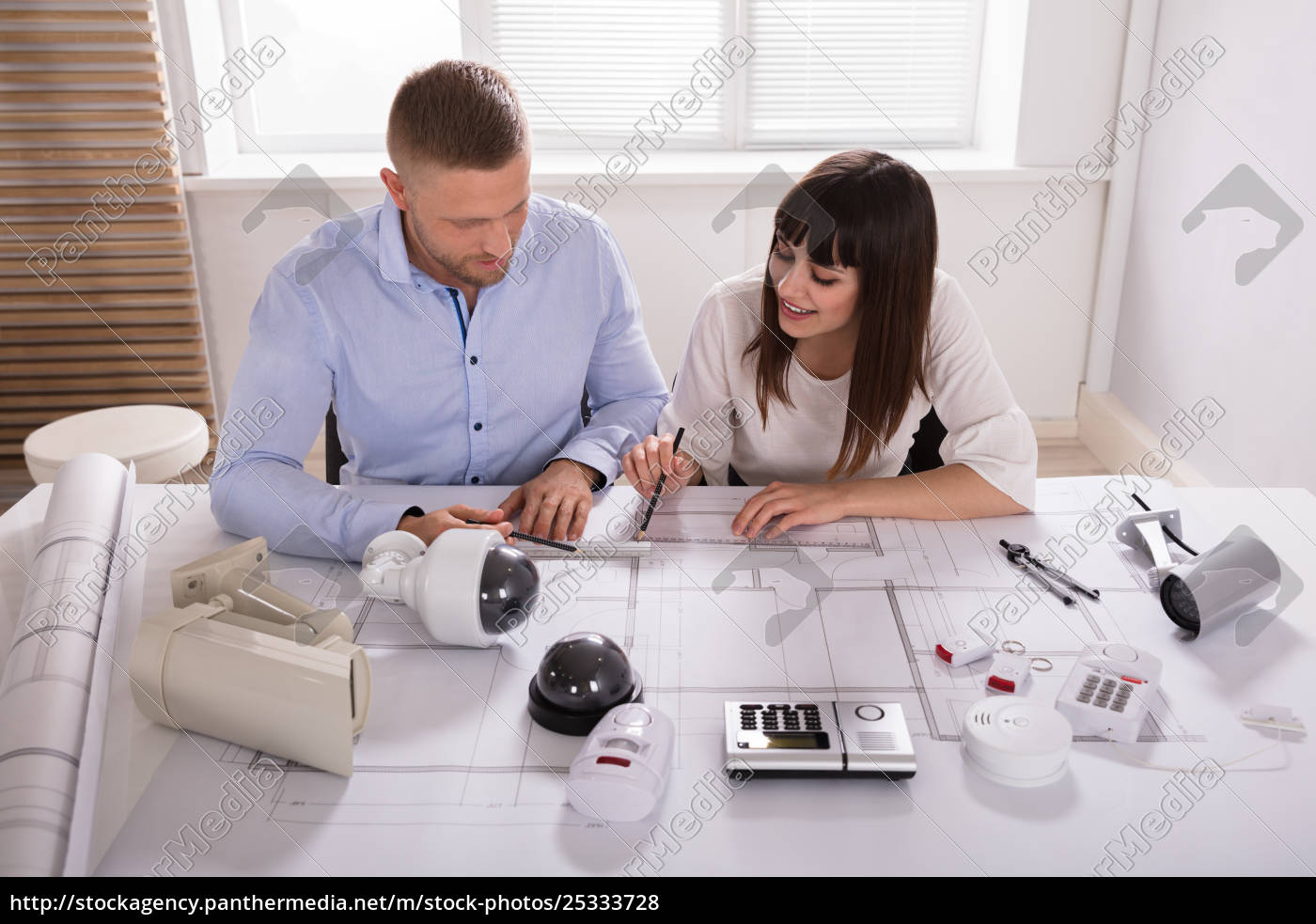 two, architects, working, on, blueprint - 25333728