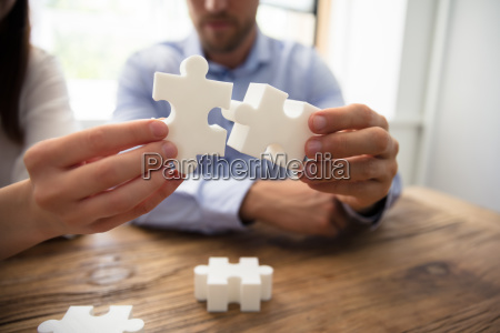 two, businesspeople, connecting, jigsaw, pieces - 25333538