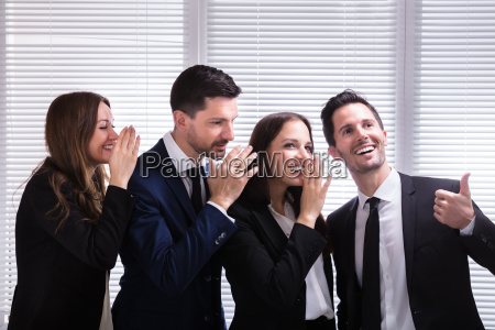 businesspeople whispering into male colleagues ear