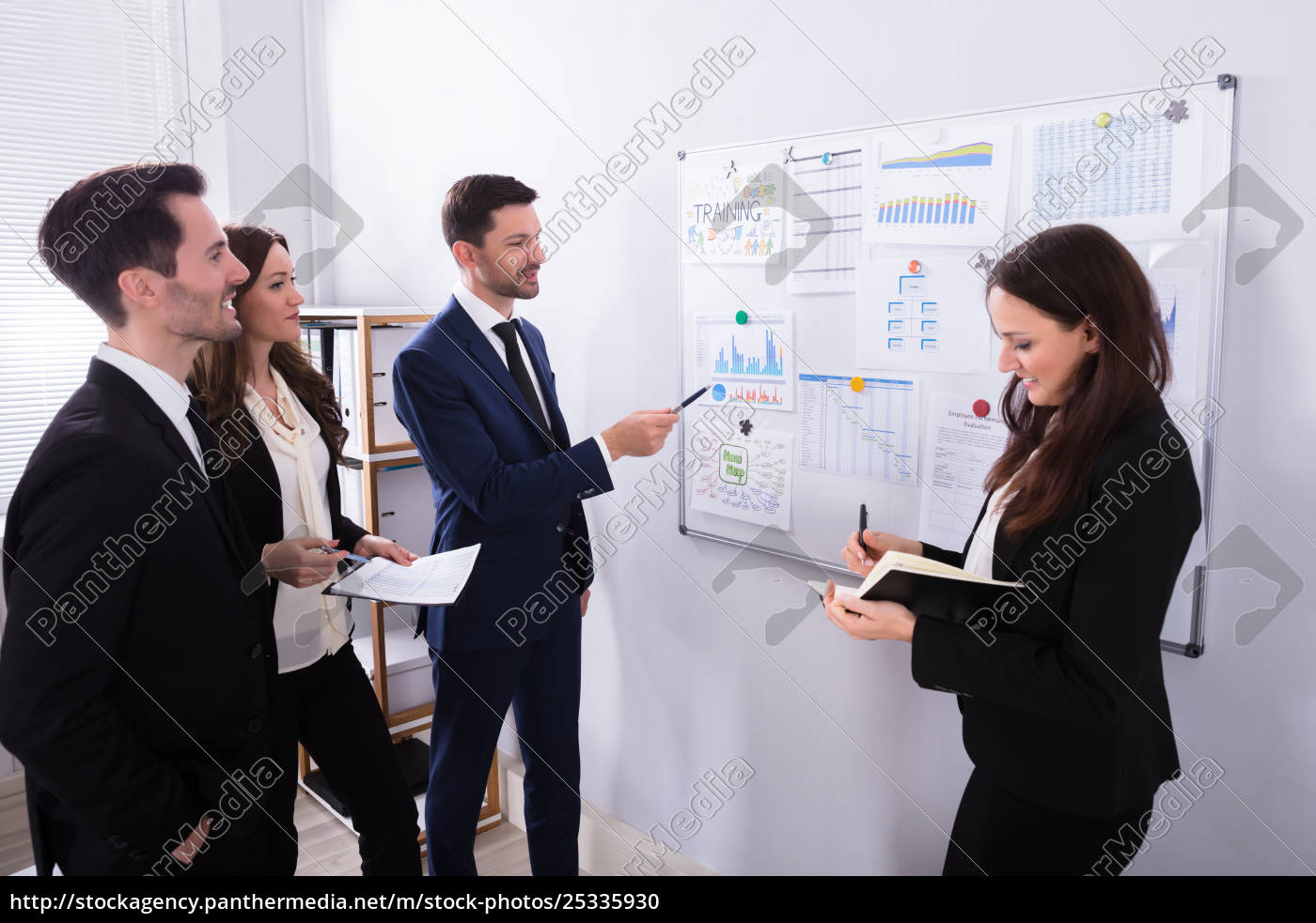 businesspeople, analyzing, graphs, on, white, board - 25335930