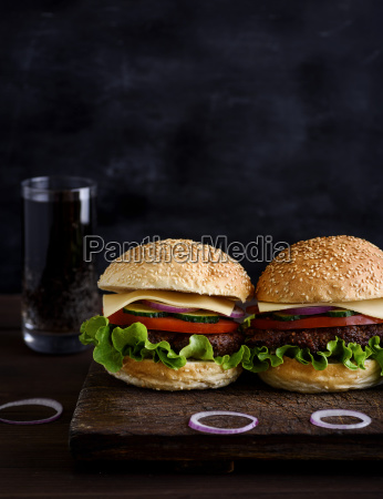 two burger with meat vegetables and