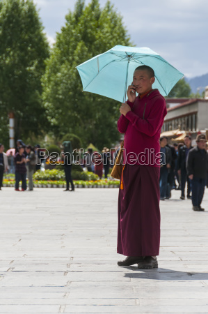 a young monk calling by cell